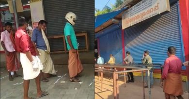 """Keralites standing in que outside a liquor shop"">"