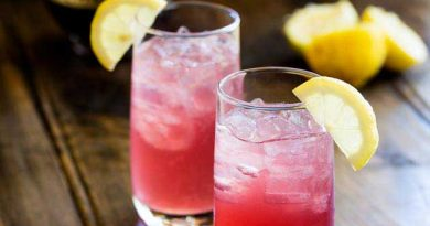 """Pink lemonade vodka cocktail on a table with lemons and bottle"">"