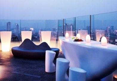 """Aer bar with chairs and lights in an outdoor seating."">"