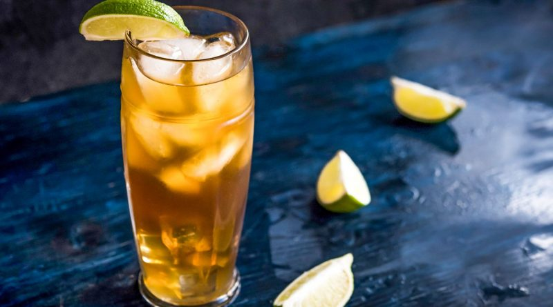 """dark and stormy cocktail with lemon and topping of ice"">"