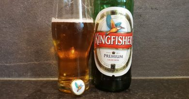 """Kingfisher premium lager beer bottle with a glass filled with the beer"">"