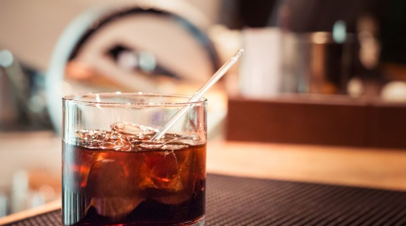 """Black russian cocktail with ice and a straw."">"